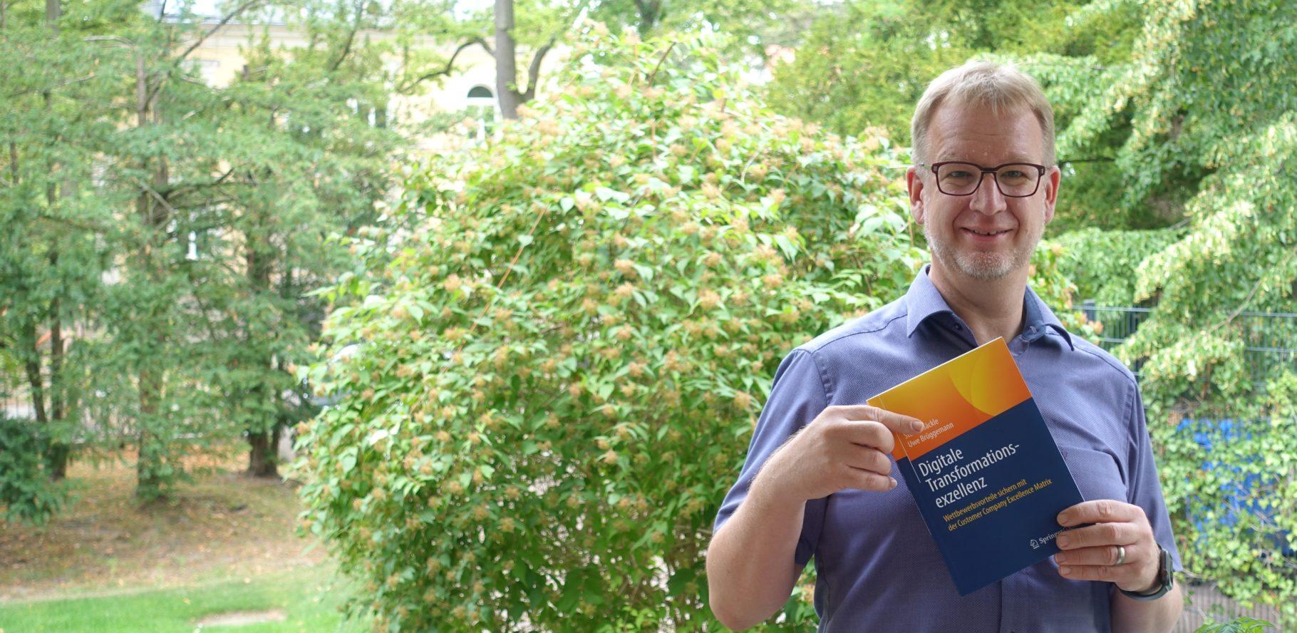 Uwe Brüggemann zeigt sein Buch über Digitalisierung